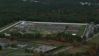 AX152_226 - 6K stock footage aerial video of a high approach toward Massachusetts Correctional Institution at Norfolk, and fall foliage, Massachusetts