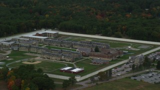 AX152_227 - 6K stock footage aerial video of a side view of Massachusetts Correctional Institution at Norfolk among fall foliage, Massachusetts