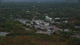 AX152_230 - 6K stock footage aerial video flying over fall foliage toward small town shops, Walpole, Massachusetts