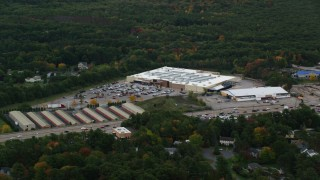 AX152_232 - 6K stock footage aerial video flying by Walmart, surrounded by trees with partial fall foliage, Walpole, Massachusetts