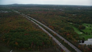 AX152_233 - 6K stock footage aerial video approaching and flying over interstate surrounded by fall foliage,Canton, Massachusetts