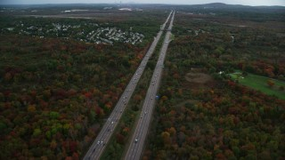AX152_234 - 6K stock footage aerial video of an Interstate near neighborhood nestled among fall foliage, Canton, Massachusetts