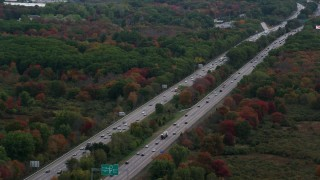 AX152_235 - 6K stock footage aerial video flying over interstate with traffic towards trees with fall foliage, Norwood, Massachusetts