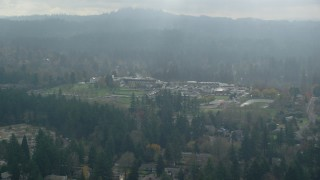 AX153_008 - 6K stock footage aerial video flying by Alpenrose Dairy Company and baseball fields with godrays, Dairyville, Portland, OR