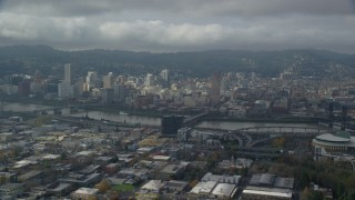 AX153_023 - 6K stock footage aerial video flying over office buildings and high-rises with view of Downtown Portland with clouds, Oregon