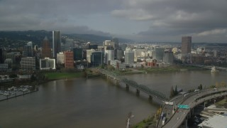 AX153_055 - 6K stock footage aerial video flying over bridge spanning Willamette River toward downtown skyscrapers and high-rises, autumn, Downtown Portland, Oregon
