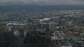 AX153_111 - 6K stock footage aerial video orbiting office buildings and Moda Center with Downtown Portland, Oregon in the background