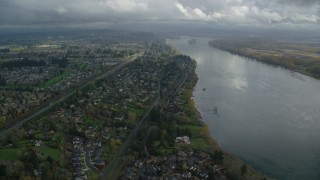 AX153_141 - 6K stock footage aerial video flying over suburban riverfront houses by Highway 14 in Vancouver, Washington