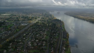AX153_142 - 6K stock footage aerial video approaching Highway 14 and fly over suburban homes on the Columbia River in Vancouver, Washington