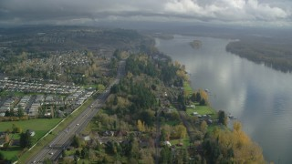 AX153_144 - 6K stock footage aerial video flying over riverfront homes between Highway 14 and the Columbia River in Vancouver, Washington