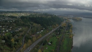 AX153_146 - 6K stock footage aerial video flying over Highway 14 to approach suburban homes in Camas, Washington