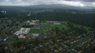 AX153_155 - 6K stock footage aerial video approaching school campus and sports fields in Camas, Washington