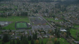 AX153_166 - 6K stock footage aerial video orbiting Washougal High School and football field in Washougal, Washington