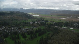 AX153_176 - 6K stock footage aerial video approaching a train traveling through Washougal, Washington