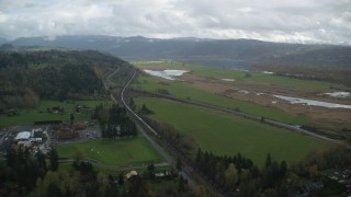 AX153_177 - 6K stock footage aerial video flying by a train traveling by fields in Washougal, Washington