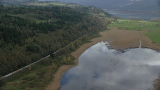 AX153_178 - 6K stock footage aerial video approaching a train traveling by fields and water in Washougal, Washington