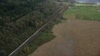 AX153_179 - 6K stock footage aerial video of a bird's eye view of a train traveling past open fields in Washougal, Washington