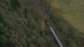 AX153_180 - 6K stock footage aerial video of a bird's eye tracking a train traveling into Columbia River Gorge, Oregon