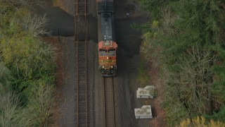 AX153_183 - 6K stock footage aerial video of a reverse view tracking a train in Columbia River Gorge, reveal trucks on country road in Oregon