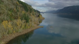 AX154_003 - 6K stock footage aerial video flying over the river and follow train tracks by the cliffs in Columbia River Gorge, Oregon