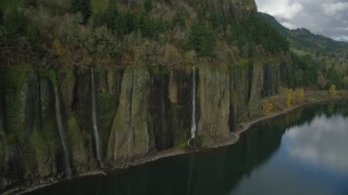 AX154_007 - 6K stock footage aerial video flying by waterfalls and railroads tracks in Columbia River Gorge, Washington