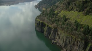 AX154_012 - 6K stock footage aerial video revealing train tracks emerging from the cliffs of Columbia River Gorge, Washington