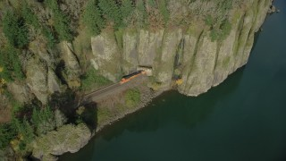 AX154_013 - 6K stock footage aerial video tracking a train as it leaves Cape Horn Railroad Tunnel in Columbia River Gorge, Washington
