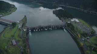 AX154_040 - 6K stock footage aerial video tilting to a bird's eye view of Bonneville Dam in Columbia River Gorge and fly over