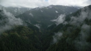 AX154_052 - 6K stock footage aerial video flying through a misty canyon to approach a mountain ridge with snow in Cascade Range, Hood River County, Oregon