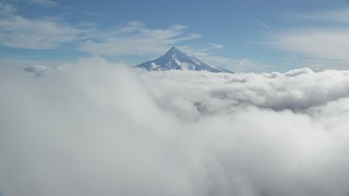 AX154_062 - 6K stock footage aerial video flying over thick cloud layer to approach snowy Mount Hood, Cascade Range, Oregon