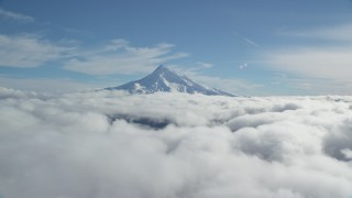 AX154_065 - 6K stock footage aerial video of the snowy summit of Mount Hood above the clouds, Cascade Range, Oregon