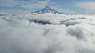 AX154_066 - 6K stock footage aerial video approaching snowy summit while flying over clouds, Mount Hood, Cascade Range, Oregon