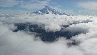 AX154_068 - 6K stock footage aerial video approaching a break in the clouds near the snowy summit of Mount Hood, Cascade Range, Oregon