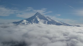 AX154_071 - 6K stock footage aerial video flying over clouds to approach Mount Hood with snow, Mount Hood, Cascade Range, Oregon