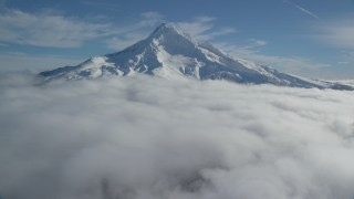 AX154_073 - 6K stock footage aerial video flying over clouds to approach Mount Hood with snow, Mount Hood, Cascade Range, Oregon