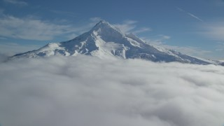 AX154_074 - 6K stock footage aerial video approaching Mount Hood summit with snow and low clouds, Mount Hood, Cascade Range, Oregon