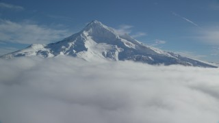 AX154_075 - 6K stock footage aerial video of a slow approach to snowy Mount Hood, surrounded by clouds, Mount Hood, Cascade Range, Oregon