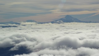 AX154_099 - 6K stock footage aerial video of Mount Jefferson and Three Sisters Volcanoes, seen above the clouds, Cascade Range, Oregon