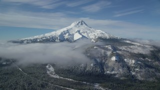 AX154_108 - 6K stock footage aerial video of low clouds over snowy forest near Mount Hood, Cascade Range, Oregon