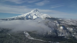 AX154_109 - 6K stock footage aerial video of low clouds over evergreen forest near the peak covered in snow, Mount Hood, Cascade Range, Oregon