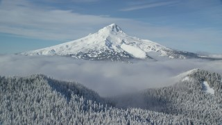 AX154_111 - 6K stock footage aerial video of low clouds and snowy forest at the base of Mount Hood, Cascade Range, Oregon