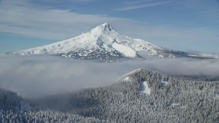 AX154_112 - 6K stock footage aerial video of Mount Hood behind low clouds and snowy forest in the Cascade Range, Oregon