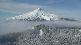 AX154_113 - 6K stock footage aerial video approaching a ridge, snowy forest and clouds near Mount Hood, Cascade Range, Oregon