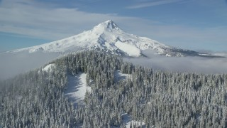 AX154_114 - 6K stock footage aerial video approaching a mountain ridge and snowy evergreens near Mount Hood, Cascade Range, Oregon