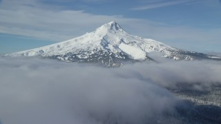 AX154_116 - 6K stock footage aerial video of snow-capped peak surrounded by low clouds, Mount Hood, Cascade Range, Oregon