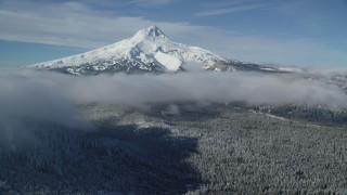 AX154_118 - 6K stock footage aerial video of snowy mountain peak with low clouds over forest, Mount Hood, Cascade Range, Oregon