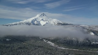 AX154_120 - 6K stock footage aerial video of low clouds over forest at the base of snow-capped Mount Hood, Cascade Range, Oregon