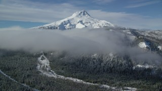AX154_121 - 6K stock footage aerial video of low clouds over forest and ridge near snow-capped Mount Hood, Cascade Range, Oregon