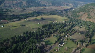 AX154_143 - 6K stock footage aerial video flying by rural farms and fields in Parkdale, Oregon