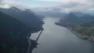 AX154_156 - 6K stock footage aerial video approaching the I-84 highway at the base of mountains in Columbia River Gorge